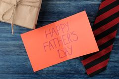 Giorno felice del ` s del padre Testo su carta, sul legame e sul regalo su una tavola di legno blu la festa degli uomini Vista su immagini stock