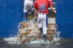 Giorno inzuppato piovoso per il giocatore di football americano che cammina nei supporti immagine stock