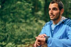 Giorno maschio adatto del pareggiatore facendo uso di uno smartwatch durante la corsa della traccia della foresta del paese trasv Immagini Stock