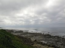 Giorno nuvoloso alla spiaggia rocciosa del villaggio di Haga-Haga, il Sudafrica Fotografie Stock