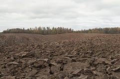 Giorno nuvoloso di autunno e primo piano del campo arato Immagini Stock Libere da Diritti