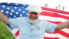 Giorno patriottico Un uomo anziano con la bandiera americana su un fondo di erba verde Celebrazione di festa dell'indipendenza de stock footage