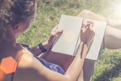 Giorno pieno di sole di estate Primo piano di un taccuino nelle mani di una giovane donna che si siede nel parco sul prato ingles fotografia stock libera da diritti