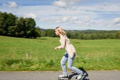 Giorno pieno di sole in linea pattinante di allenamento di velocità della giovane donna Fotografia Stock
