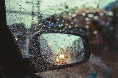 Giorno piovoso sulla strada, gocce di pioggia sullo specchio di automobile con lo specchietto retrovisore esterno laterale Fotografia Stock