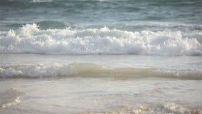 Giorno ventoso, onda del mare che schianta spiaggia sabbiosa il giorno soleggiato, primo piano del teleobiettivo video d archivio