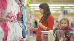 Giovane acquisto attraente della madre per i vestiti dei bambini negli oggetti di vendita al dettaglio di un'osservazione del neg archivi video