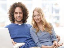 Giovane acquisto sorridente delle coppie sul Internet Fotografia Stock Libera da Diritti