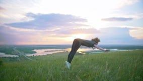 Giovane acrobata femminile che esegue una vibrazione attraverso il sole al tramonto video d archivio