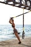Giovane addestramento allegro della ragazza con il trx vicino al mare di mattina Fotografie Stock Libere da Diritti