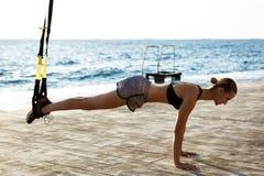 Giovane addestramento allegro della ragazza con il trx vicino al mare di mattina Immagini Stock