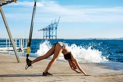 Giovane addestramento allegro della ragazza con il trx vicino al mare di mattina Fotografie Stock