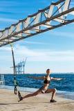 Giovane addestramento allegro della ragazza con il trx vicino al mare di mattina Immagini Stock Libere da Diritti