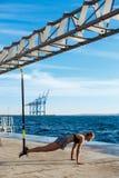 Giovane addestramento allegro della ragazza con il trx vicino al mare di mattina Immagine Stock