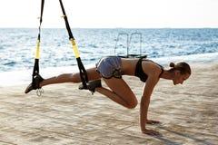 Giovane addestramento allegro della ragazza con il trx vicino al mare di mattina Fotografia Stock