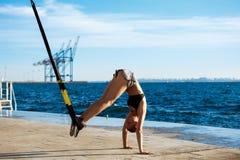 Giovane addestramento allegro della ragazza con il trx vicino al mare di mattina Immagine Stock Libera da Diritti