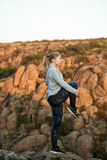 Giovane addestramento allegro della ragazza, sctretching sulla roccia in canyon Fotografie Stock