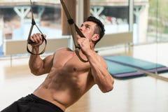 Giovane addestramento attraente dell'uomo con le cinghie di forma fisica di Trx Immagini Stock