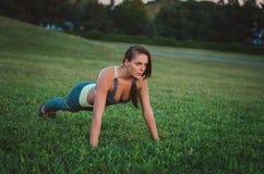 Giovane addestramento attraente della donna nel parco Plancia di esercizio misura Immagini Stock Libere da Diritti