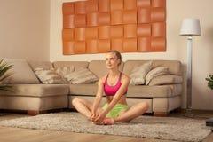 Giovane addestramento biondo di forma fisica della sportiva a casa Fotografia Stock Libera da Diritti