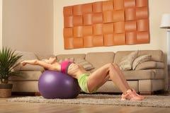 Giovane addestramento biondo di forma fisica della sportiva a casa Immagine Stock Libera da Diritti