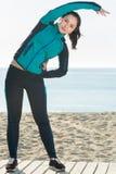 Giovane addestramento sorridente della donna sulla spiaggia dal mare Immagine Stock Libera da Diritti