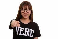 Giovane adolescente asiatico felice del nerd che sorride e che indica dito fotografia stock