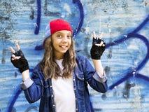 Giovane adolescente biondo sveglio della ragazza in una camicia del denim e del berretto da baseball su un fondo della parete di  Immagini Stock
