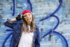 Giovane adolescente biondo sveglio della ragazza in una camicia del denim e del berretto da baseball su un fondo della parete di  Fotografia Stock