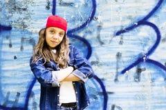 Giovane adolescente biondo sveglio della ragazza in una camicia del denim e del berretto da baseball su un fondo della parete di  Immagini Stock Libere da Diritti