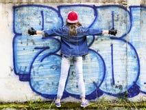 Giovane adolescente biondo sveglio della ragazza in una camicia del denim e del berretto da baseball su un fondo della parete di  Fotografie Stock