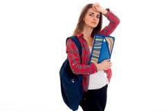 Giovane adolescente castana adorabile degli studenti in vestiti alla moda e zaino sulla sua posa delle spalle isolati su bianco Fotografie Stock Libere da Diritti