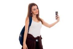 Giovane adolescente castana attraente degli studenti in vestiti alla moda e zaino sulla sua posa delle spalle isolati su bianco Immagine Stock