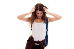 Giovane adolescente castana stanco degli studenti in vestiti alla moda e zaino sulla sua posa delle spalle isolati su bianco Immagine Stock Libera da Diritti