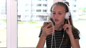 Giovane adolescente che canta avanti alla sua musica stock footage