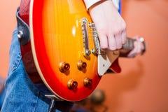 Giovane adolescente che gioca sulla chitarra elettrica, fuoco sul bottone di tono immagini stock
