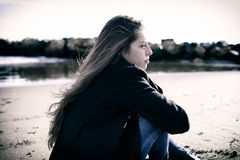 Giovane adolescente che ritiene seduta diminuita davanti alla spiaggia Fotografia Stock Libera da Diritti