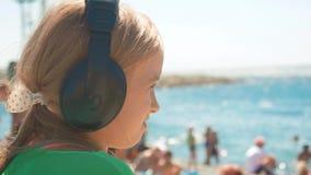 Giovane adolescente che si siede dalla spiaggia di sabbia bianca che ascolta la musica facendo uso delle cuffie e dello smartphon video d archivio