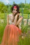 Giovane adolescente grazioso che si siede contro i fiori Fotografia Stock