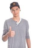 Giovane adolescente maschio attraente con il pollice su isolato su bianco. Fotografia Stock