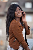 Giovane adolescente nero che per mezzo di un telefono mobile Fotografie Stock