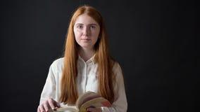 Giovane adolescente sveglio con il libro di lettura dei capelli dello zenzero ed esaminare macchina fotografica, stante isolata s stock footage