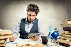 Giovane adulto che legge un libro elettronico Fotografia Stock
