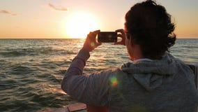 Giovane adulto che prende tre foto del Sun che cadono sopra l'orizzonte archivi video