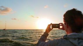 Giovane adulto che prende tre foto del Sun che cadono sopra l'orizzonte stock footage