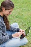 Giovane adulto sorridente che si siede a gambe accavallate Fotografia Stock