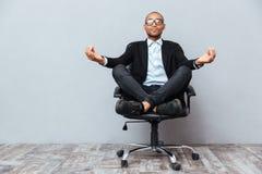 Giovane africano rilassato che si siede e che medita su sedia dell'ufficio fotografia stock