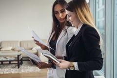 Giovane agente immobiliare che mostrano appartamento e che discutono il contratto ed altri documenti con un cliente Fotografia Stock Libera da Diritti