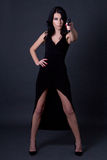 Giovane agente segreto sexy della donna in vestito nero che posa con il ove della pistola immagini stock