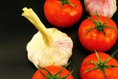 Giovane aglio con i pomodori succosi rossi su fondo nero immagini stock libere da diritti